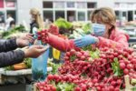 women selling radishes at a farmers market